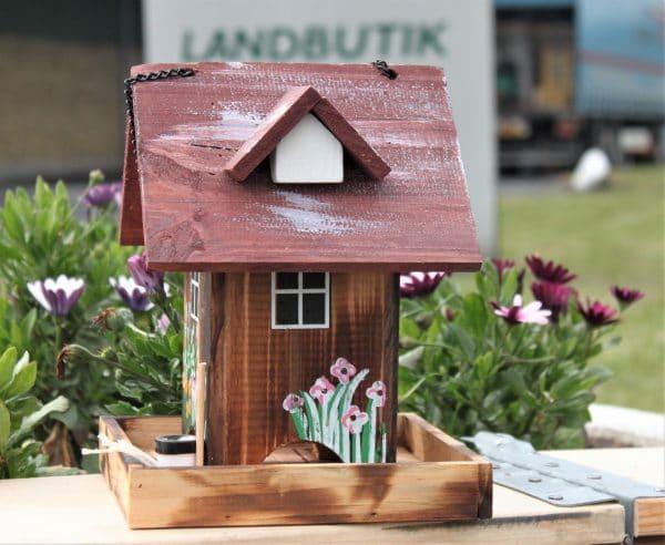 Farverigt fuglehus, der ligner et lille hus