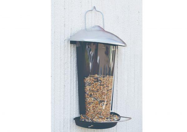 Fuglefoderautomat på væg med fuglefoder